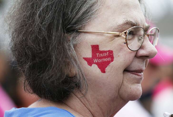 Kathleen Stein wears a temporary tattoo on her check as she attends a rally in support of Planned Parenthood on Saturday, Feb. 11, 2017. Following the Women's March in Washington last month, three San Antonio women organized a rally on Saturday with about 200 supporters on the city's Westside to rally in support of the organization. Supporters cited women's rights to govern their own bodies amongst some of the key reasons for keeping the non-profit organization that provides health services for women operational and funded. People at the rally lined Commerce Street and waved signs in support of Planned Parenthood. Speeches from concerned citizens were heard as supporters cheered and applauded at Sabinas Coffee Shop. (Kin Man Hui/San Antonio Express-News)