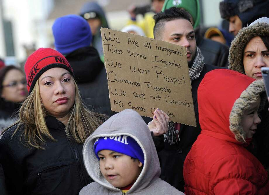"""Ingrid Vasquez of Danbury, a native of Guatemala, holds a sign in two languages at a """"day without immigrants"""" rally at Danbury City Hall Thursday, February 16, 2017. Her son Alexander Hernandes, 7, is next to her. Photo: Carol Kaliff / Hearst Connecticut Media / The News-Times"""