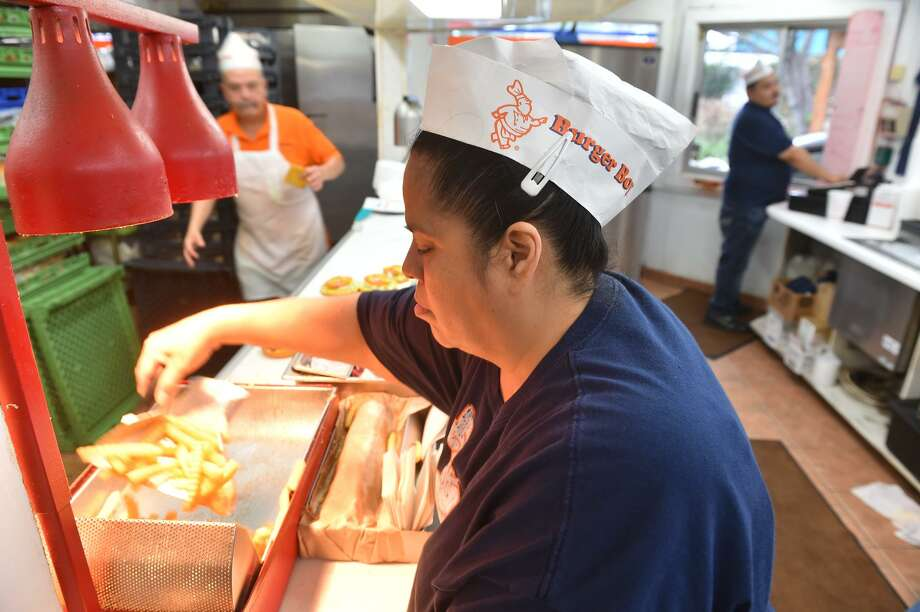 Mary Garcia packages up french fries for customers at the original Burger Boy on North St. Mary's Street. Photo: Express-News File Photo / ROBERT JERSTAD