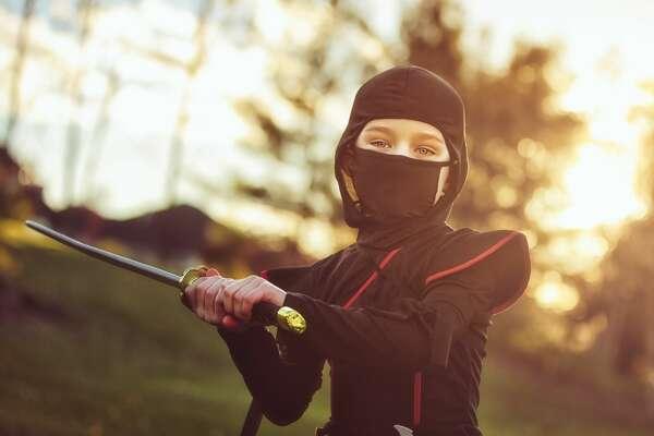 Boy, holding a sword, dressed up as a ninja.