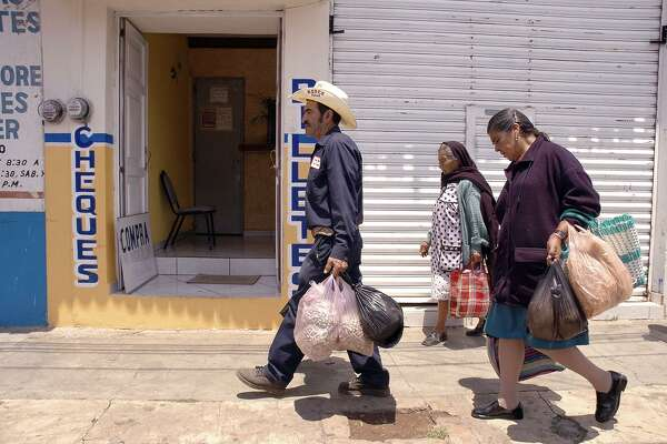 "José Ortíz (center) carries groceries through Villa Morelos with his wife Josefina Chávez Pérez (right). Ortíz is one of about a half-dozen San Angel natives and former IFCO Sytems pallet builders in San Antonio who were rounded up in a immigration raids last month. He was wearing Texas Pallet overalls and a cowboy hat with ""Texas Rodeo"" embroidered on it. Such raids sow fear and will ultimately hurt Texas."