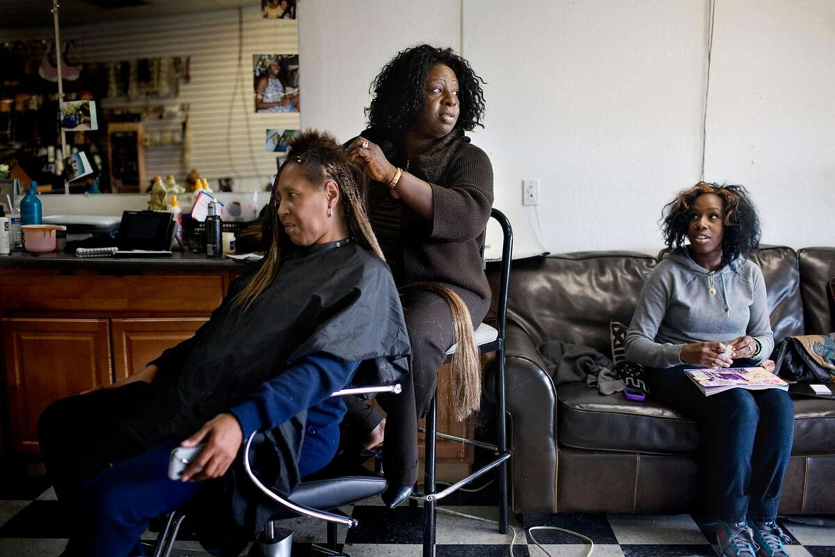 Doris Campbell braids the hair of Annie Davis, in her beauty shop, My African Heritage, in Vallejo.