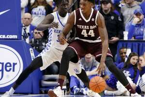 Texas A&M's Robert Williams (44) drives while defended by Kentucky's Wenyen Gabriel during the first half of an NCAA college basketball game, Tuesday, Jan. 3, 2017, in Lexington, Ky. (AP Photo/James Crisp)