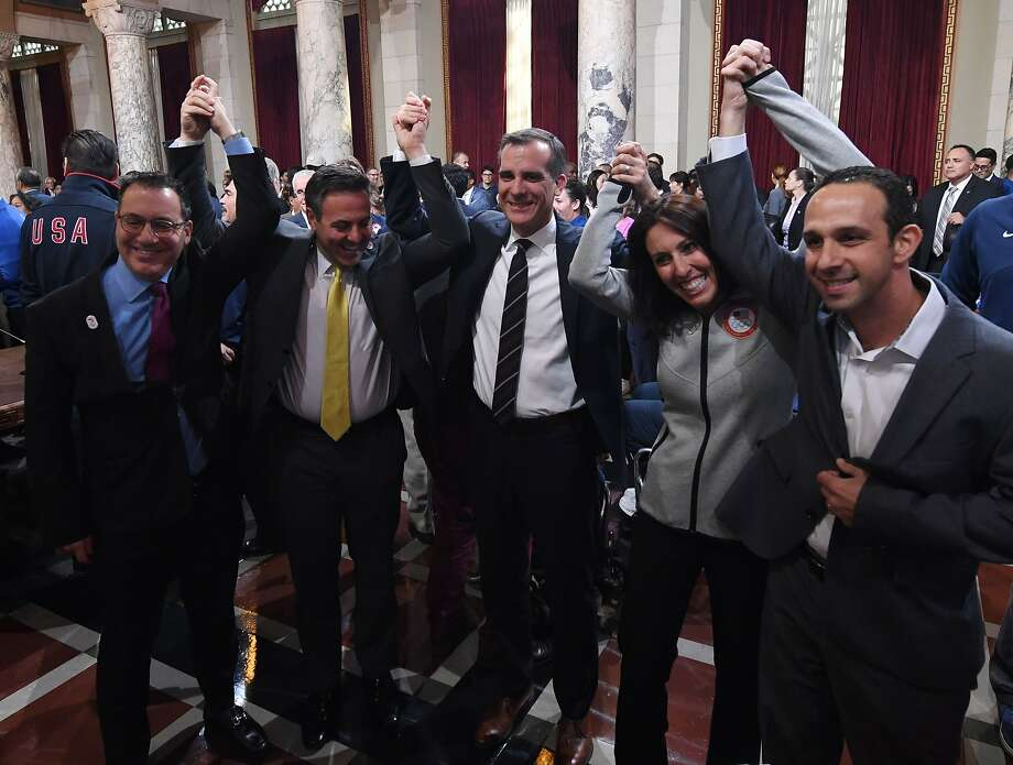 Mayor Eric Garcetti (C) and former Olympian Janet Evans (R) celebrate with City Councillors after the Los Angeles City Councils 13-0 unanimous final approval vote to bid for the 2024 Summer Olympics in Los Angeles. Photo: MARK RALSTON, AFP/Getty Images