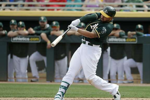Oakland Athletics' Yonder Alonso hits a home run against the San Francisco Giants during the second inning of a spring training baseball game in Mesa, Ariz., Friday, March 3, 2017. (AP Photo/Chris Carlson)