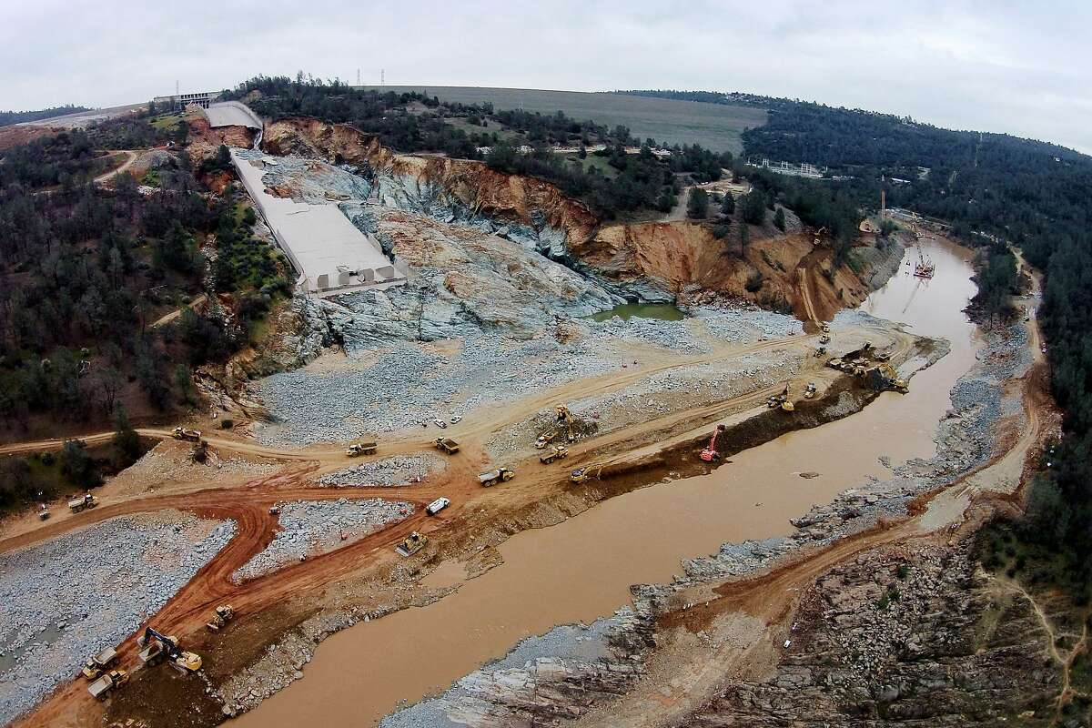 The damaged main spillway of the Oroville Dam is seen at the top left, as officials continue to work on clearing debris from the bottom on Friday, March 3, 2017, in Oroville, Calif.