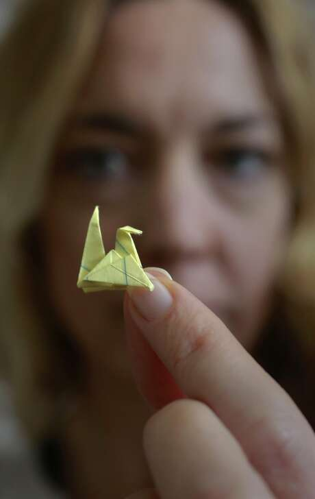 Social worker Erin Maxwell shows an origami figure given by her client, a 14-year-old boy who fled extreme child abuse in Honduras and arrived in the U.S. with no one to take him in. Photo: Michael Macor, The Chronicle
