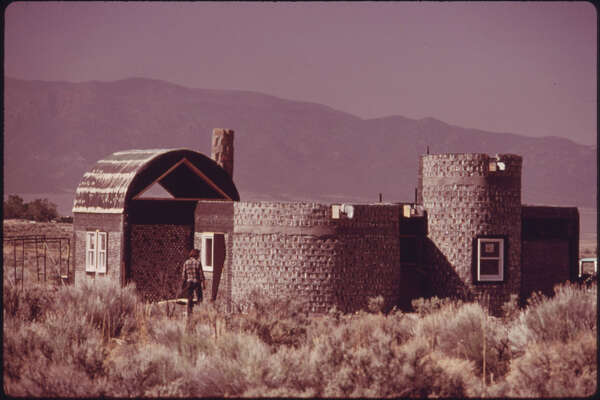 """Original caption: """"Another experimental house made of empty steel beer and soft drink can construction near Taos, New Mexico. This house will be plastered with adobe like the other homes in the area, but will have cost up to 20 percent less, according to architect Michael Reynolds."""" David Hiser photo, courtesy National Archives."""