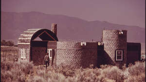 "Original caption: ""Another experimental house made of empty steel beer and soft drink can construction near Taos, New Mexico. This house will be plastered with adobe like the other homes in the area, but will have cost up to 20 percent less, according to architect Michael Reynolds."" David Hiser photo, courtesy National Archives."