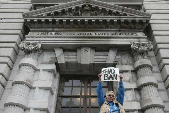 FILE - In this Feb. 7, 2017, file photo, Karen Shore holds up a sign outside of the 9th U.S. Circuit Court of Appeals in San Francisco, Calif. President Donald Trump's administration said in court documents on Thursday, Feb. 16, 2017, it wants an end to the legal fight over its ban on travelers from seven predominantly Muslim nations and will instead issue a replacement ban.  (AP Photo/Jeff Chiu, File)