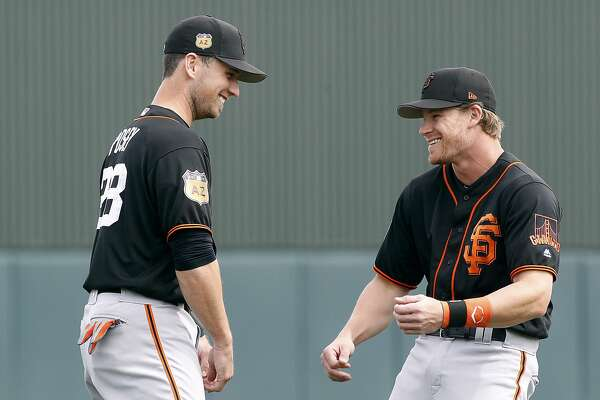 San Francisco Giants catcher Buster Posey, left, jokes around with teammate Gordon Beckham before a Spring Training game against the Oakland Athletics at Hohokam Stadium in Mesa, AZ. on Friday, March 3, 2017.  With the hyper-partisan political climate, players are hesitant to talk politics or voice their views in order to keep team unity and chemistry in the clubhouse.