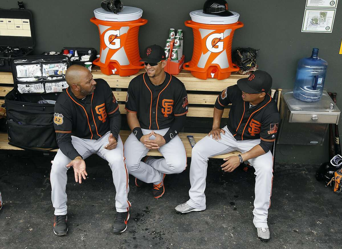 San Francisco Giants first base coach Jose Alguacil, left, talks with players Gorkys Hernandez, center, and Juniel Querecuto, before a Spring Training game against the Oakland Athletics at Hohokam Stadium in Mesa, AZ. on Friday, March 3, 2017. With the hyper-partisan political climate, players are hesitant to talk politics or voice their views in order to keep team unity and chemistry in the clubhouse.