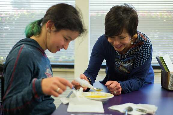 "Melis Diken, who has Cerebral Palsy, and her mother Pamela, right, examine a Liftware Steady spoon made by Verily that counters shaking at the Silicon Valley Independent Living Center in San Jose, Calif. on Friday, March 3, 2017. Verily is part of a category of companies classified as ""Other Bets"" which represent a small portion of Alphabet's revenue."