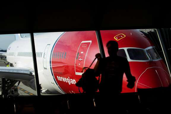 A passenger prepares to board a Stockholm-bound Norwegian Air flight at Oakland International Airport on Friday, March 3, 2017, in Oakland, Calif.