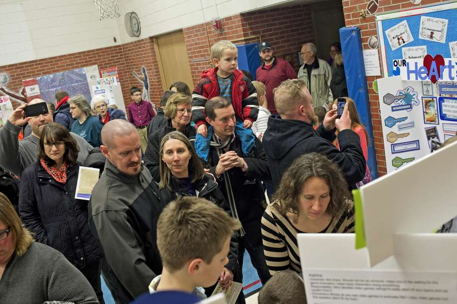 Attendees browse presentations during the Primary Years Programme (PYP) exhibition on Thursday at Plymouth Elementary School. Plymouth Elementary was the first authorized International Baccalaureate PYP World School in the Midland Public Schools district. Fifth-graders divided into teams of three to four students, chose a project or issue that interested them and then worked with the help of a community member as their mentor. Project topics ranged from animal abuse to pollution to music. Photo: Erin Kirkland/Midland Daily News