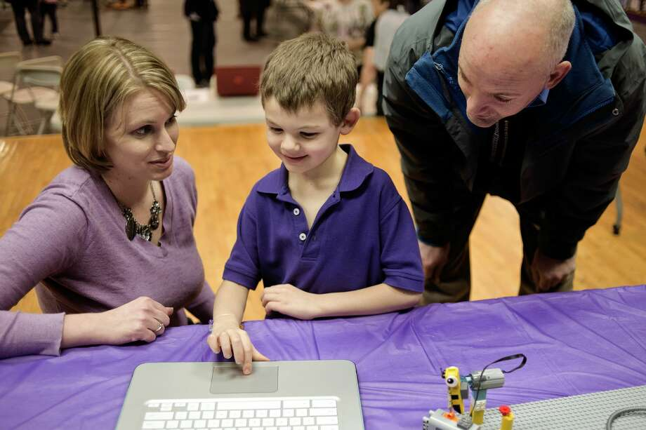 "Calvary Baptist robotics coach Jaime Fisk shows first grader Caleb McIntyre, 7, center, and father Scott McIntyre how to control a Lego mouse during an art and academics fair focused on STEM on Friday at Calvary Baptist. The gymnasium was full of art projects, STEM demonstrations, the school's new 3D printer and History Day and science presentations.  ""You hear about all the schools that are doing STEM, and people look at us and say you're a small school, you can't do that,"" teacher and registrar Mary Hillebrand said. ""I want people to know that we do it, and we do it well."" The junior Lego league program, which is for children in kindergarten through third grade, programmed and created animals and their habitats. Photo: Erin Kirkland/Midland Daily News"