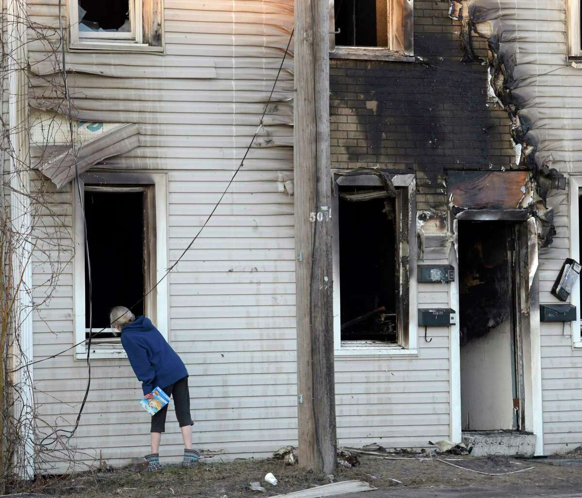 A resident of 1366 Central Avenue looks in the window of her house after a fire destroyed the dwelling Friday Mar. 4, 2017 in Colonie, N.Y. (Skip Dickstein/Times Union)
