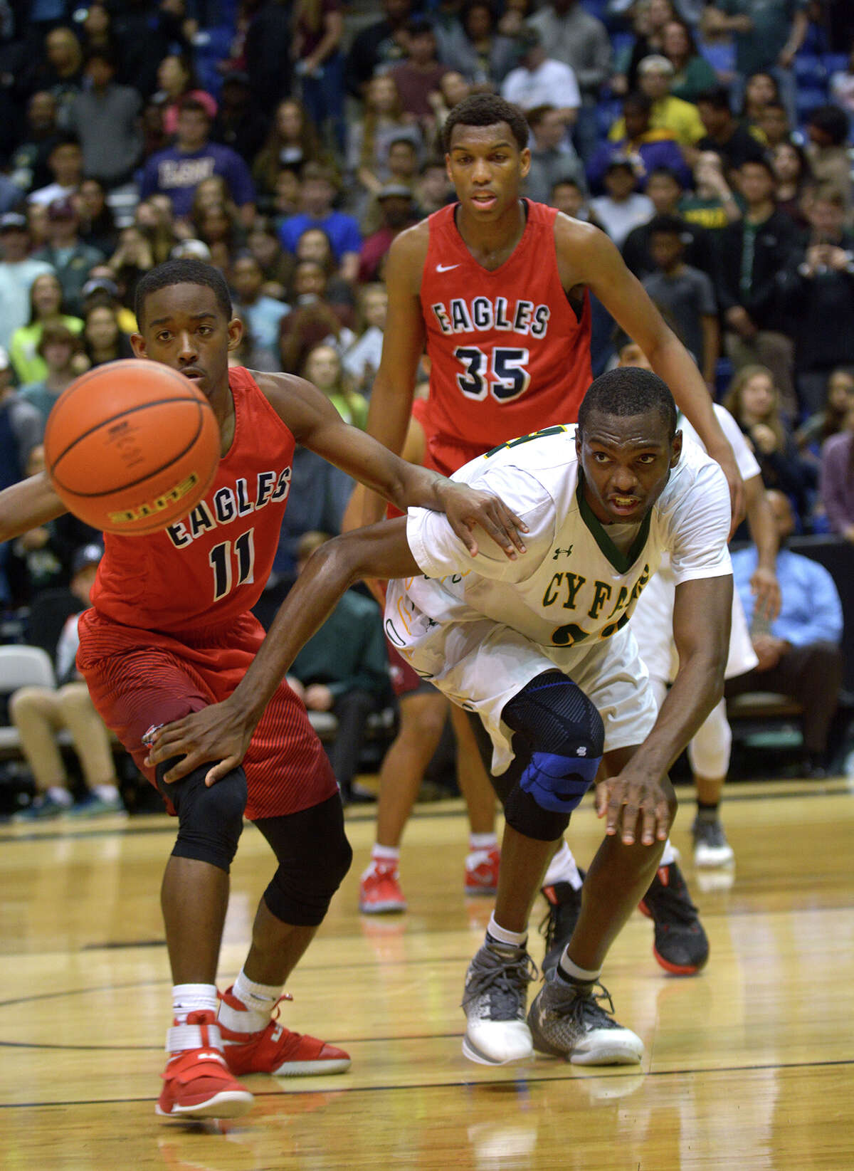 Atascocita junior guard Jakory Champagne (11) hustles for a loose ball with Cy Falls junior forward Deshang Weaver during the 4th quarter of their Class 6A Region III Boys Basketball semifinal at the Richard E. Berry Center in Cypress on Friday, March 3, 2017. (Photo by Jerry Baker/Freelance)