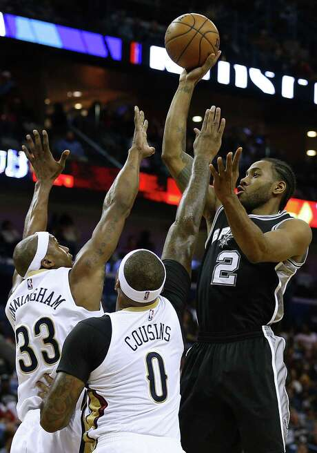 NEW ORLEANS, LA - MARCH 03: Kawhi Leonard #2 of the San Antonio Spurs shoots over Dante Cunningham #33 of the New Orleans Pelicans and DeMarcus Cousins #0 during the first half of a game at the Smoothie King Center on March 3, 2017 in New Orleans, Louisiana. NOTE TO USER: User expressly acknowledges and agrees that, by downloading and or using this photograph, User is consenting to the terms and conditions of the Getty Images License Agreement. Photo: Jonathan Bachman, Getty Images / 2017 Jonathan Bachman