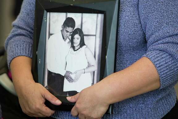A supporter of Jose and Rose Escobar holds a photo of the couple during a news conference in opposition against mass deportation, and to also speak out against the deportation of Jose Escobar on Friday, March 3, 2017, in Houston. Escobar was deported back to El Salvador on Thursday, a country has hasn't been to in more than 15 years.