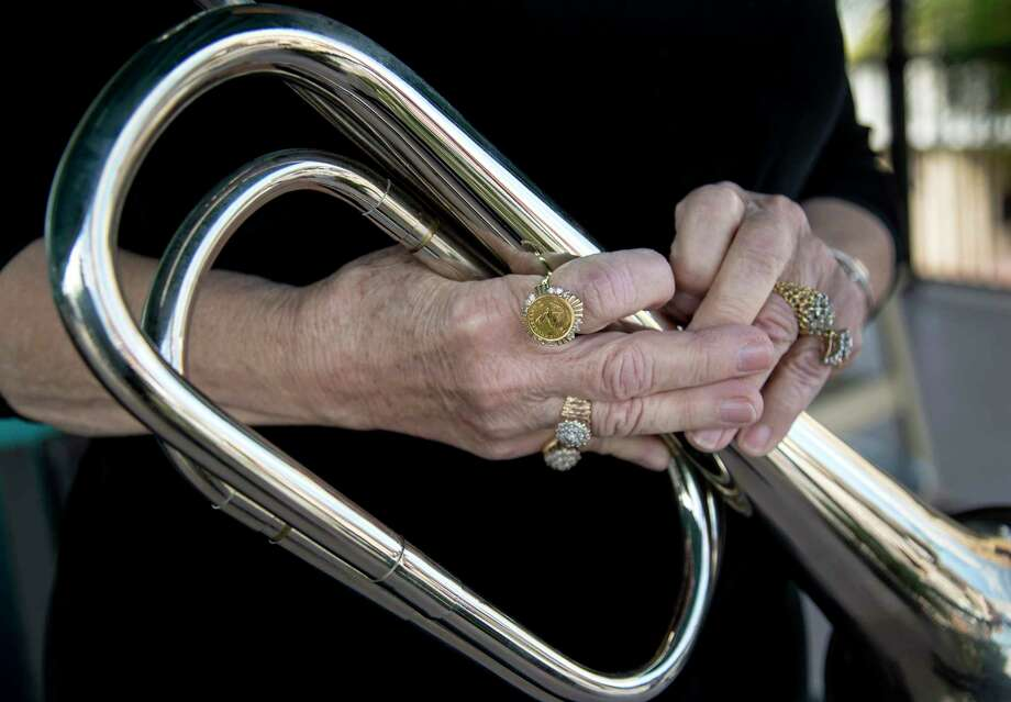 Joan Taylor holds a bugle that belonged to her late husband, Guy Taylor, Sr., during a portrait session on her balcony, overlooking the intersection of 21st Street and Post Office Street, Friday, March 3, 2017, in Galveston. Her late husband, a Korean War veteran, made a daily ritual of playing taps from the balcony, as Constable Clint Brown blocked the intersection below and stood at attention. Photo: Jon Shapley, Houston Chronicle / © 2017  Houston Chronicle