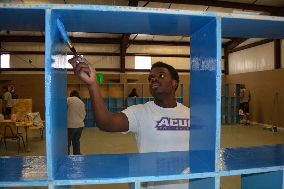 Jamil Easley, a Wayland freshman from Waxahachie, uses a dark shade of primary blue to paint one of the cubbies in the gym at Wee Care Child Center, 2305 Yonkers. Almost two dozen Wayland students spent Friday evening and all day Saturday brightening up the facility.