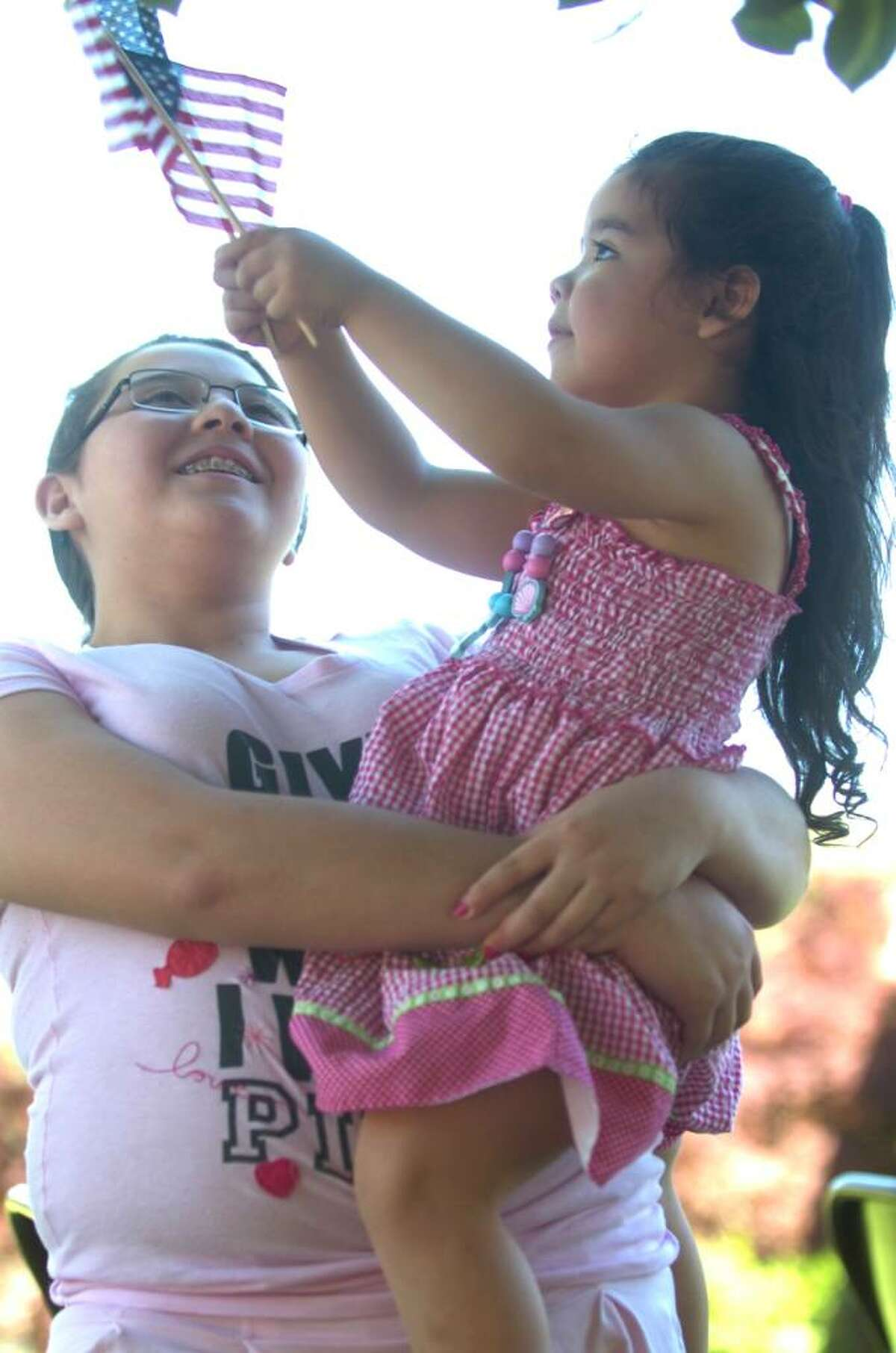 Fernenda Moreno, 12, carries her sister Camila, 3, at the Bryam parade on Sunday, May 30, 2010.