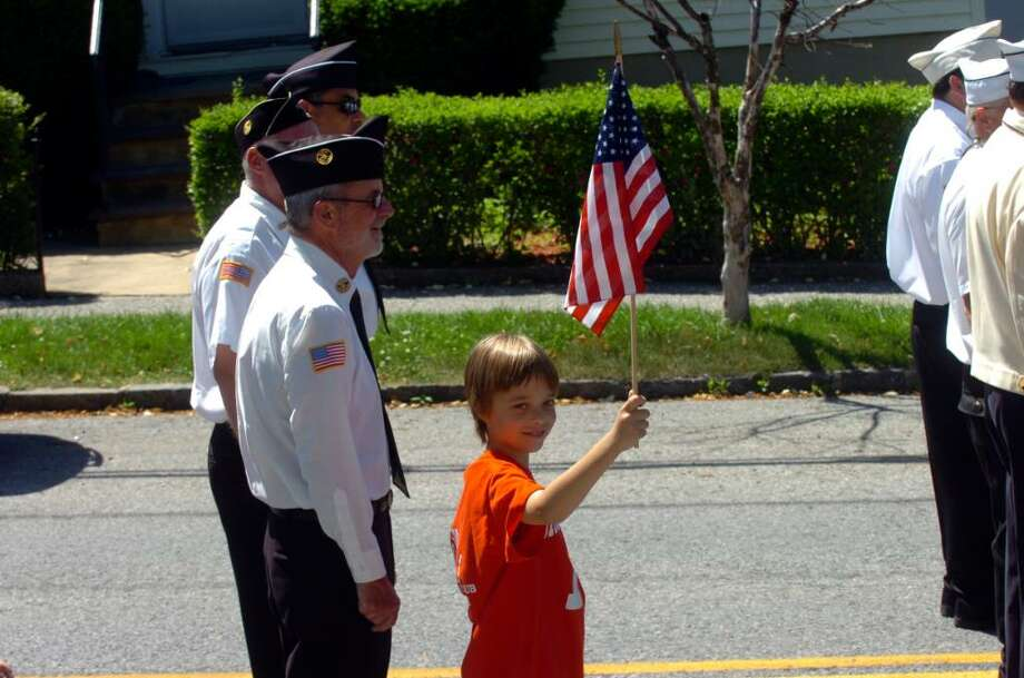 Kevin Wing, 10, waves an American flag while walking with his grandfather Bill Wing, left, at the Byram Memorial Day parade on Sunday, May 30, 2010. Photo: Helen Neafsey / Greenwich Time