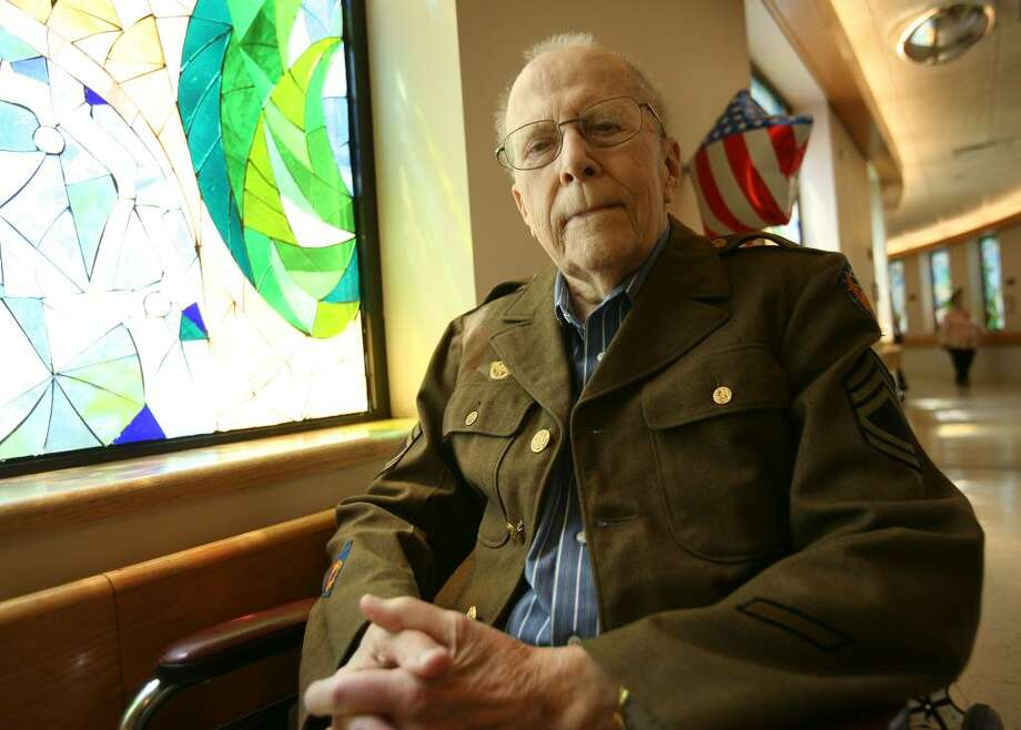 Veteran Frank Olsson tries on his World War 2 uniform at the Jewish Home for the Elderly in Fairfield, where he resides. Olsson, who turns 94 on Memorial Day, serviced the planes, including the Enola Gay, that dropped the atomic bomb on Japan. Photo: Brian A. Pounds / Connecticut Post