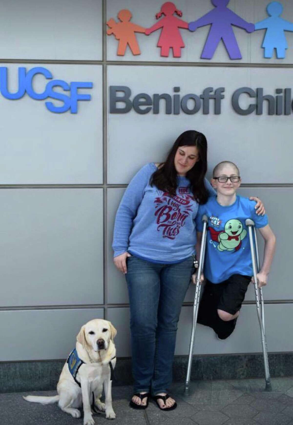 Quinn with his mother, Teresa Howell, and a service dog.
