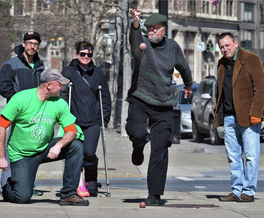 Ed Collins of Niskayuna, center, hurls the bowl or bullet during a demonstration of Irish Road Bowling at the Irish American Heritage Museum's Fifth Annual Irish Soda Bread Competition Saturday March 4, 2017 in Albany, NY.  (John Carl D'Annibale / Times Union) Photo: John Carl D'Annibale / 20039795A