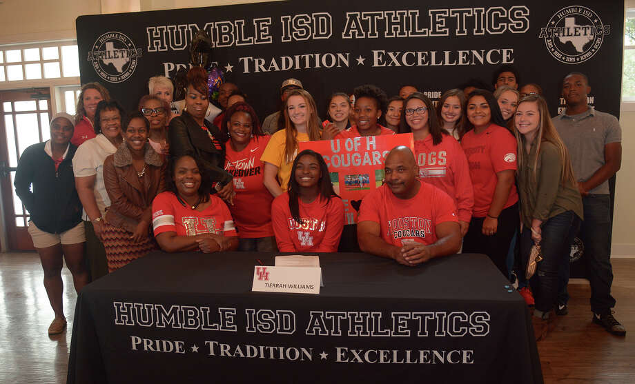 Tierrah Williams, center, a senior and varsity softball player at Atascocita High School, flanked by her mom, Nicole, left, and dad, Clifton, is all smiles after signing her commitment letter with the University of Houston on Humble ISD Signing Day at Atascocita Country Club on Wednesday, Nov. 9, 2016. (Photo by Jerry Baker/Freelance) Photo: Jerry Baker, Freelance / Freelance