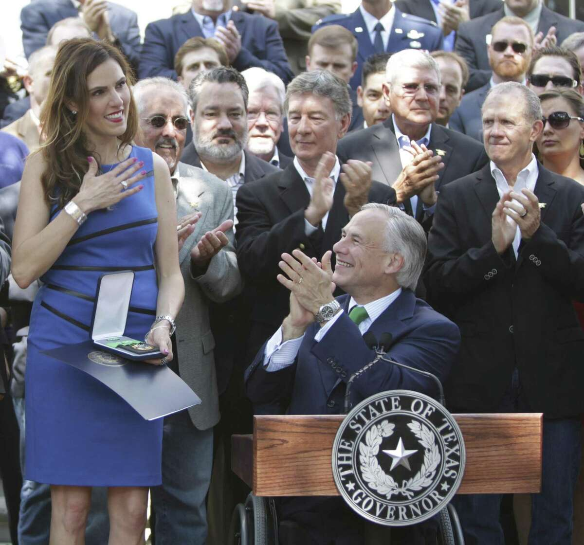 Taya Kyle, left, reacts Wednesday Aug. 26, 2015 after receiving her husband, Chief Petty Officer Chris Kyle's posthumous Texas Legislative Medal of Honor during a ceremony on the grounds of the governor's mansion. Behind her are veterans and current service members.