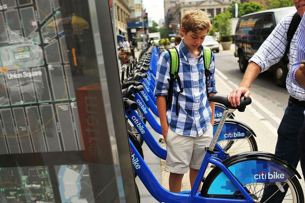 People look at Citi Bikes at a docking station in New York's Union Square. New York's program has grown faster than San Francisco's.