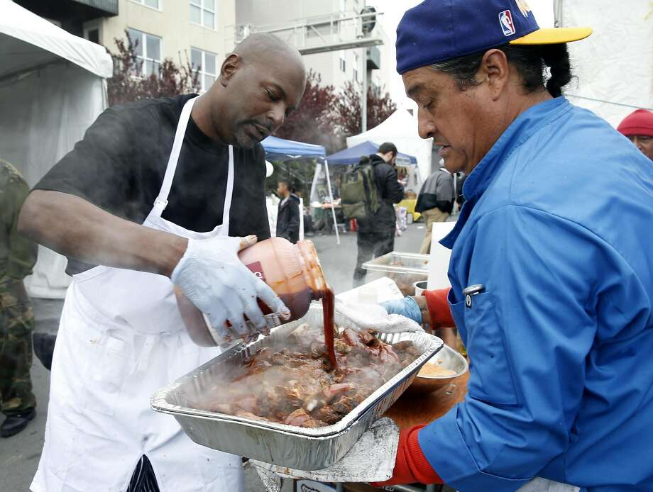 Charles Adams (left) and Jose Tovar finish a tray of pork ribs with barbecue sauce at the Black Cuisine Festival in San Francisco's Bayview district. Photo: Paul Chinn, The Chronicle