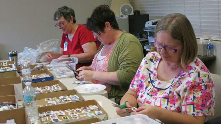 Char Isham, 60, of Mattawan, Mich., right, Michele Whitlock, 50, of Big Fork, Mont., center, and Dianne Archer, 71, of Poughkeepsie, N.Y., volunteer in the postage-stamp ministry at Wycliffe Associates in southeast Orange County, Fla. The stamps are sold to benefit the organization's work of helping translate the Bible around the world. (Susan Jacobson/Orlando Sentinel/TNS)