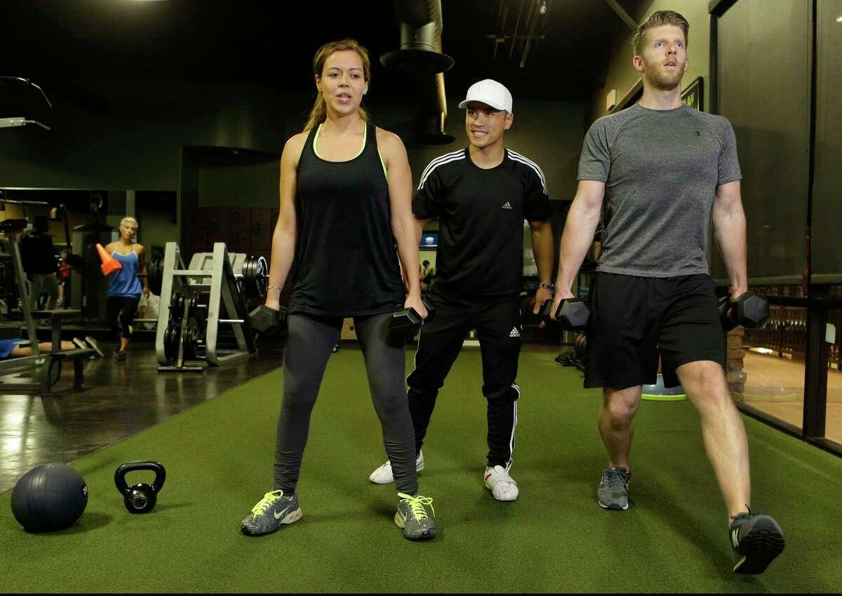 """Houston Fit Reality"" trainer David T. Nguyen, center, works with Jennifer Heflin, and her husband, Eric Heflin."