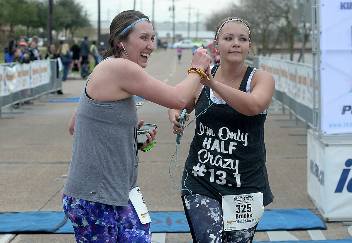 Cousins Brandi Brister (left) and Brooke Brister celebrate as they finish their half marathon during the 8th annual Gusher Marathon Saturday in Beaumont. Photo taken Saturday, March 4, 2017 Kim Brent/The Enterprise