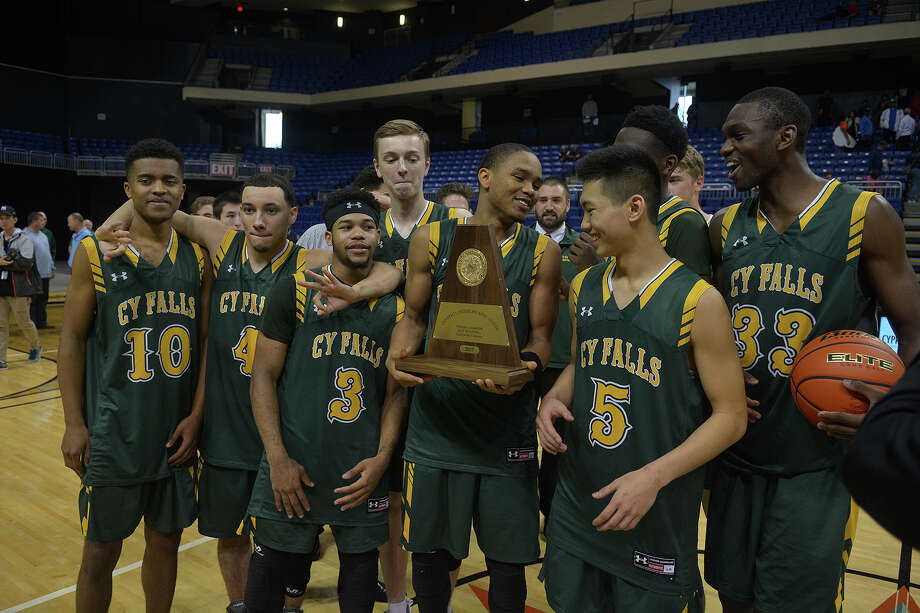 Cy Falls junior guard Nigel Hawkins, center, hold the team trophy as the Eagles celebrate after their Class 6A Region III Boys Basketball final win over Fort Bend Bush at the Richard E. Berry Center in Cypress on Saturday, March 4, 2017. (Photo by Jerry Baker/Freelance) Photo: Jerry Baker, For The Chronicle / Freelance