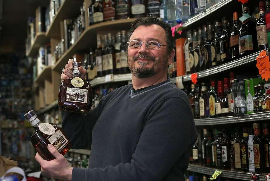 Owner and spirits connoisseur Sam Salfiti shows his bourbon at Save-More Market. Photo: Liz Hafalia, The Chronicle