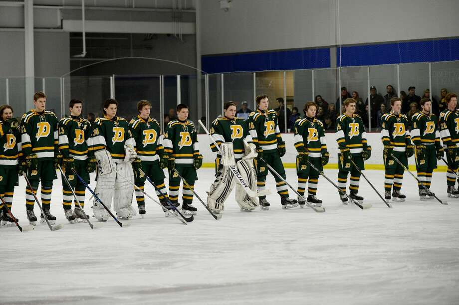 The Chargers stand on the ice during player introductions before their game against Hartland on Saturday at the Midland Civic Arena. Hartland won the game 5-0. Photo: NICK KING | Nking@mdn.net
