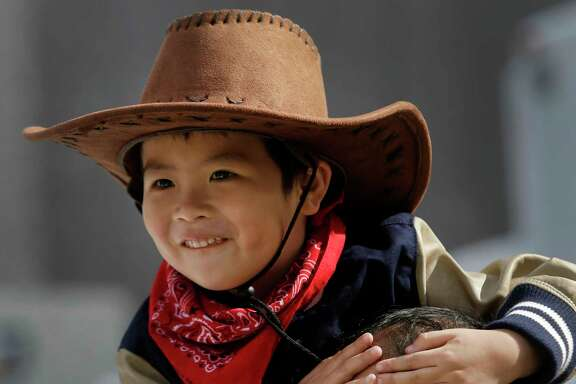 Henry Li, 5, sitting on the shoulders of his dad, Yining Li, was among the hundreds of spectators downtown for the Houston Livestock Show and Rodeo parade Saturday.