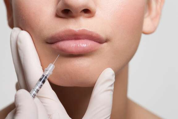 Close up of woman receiving botox injection in lips   x