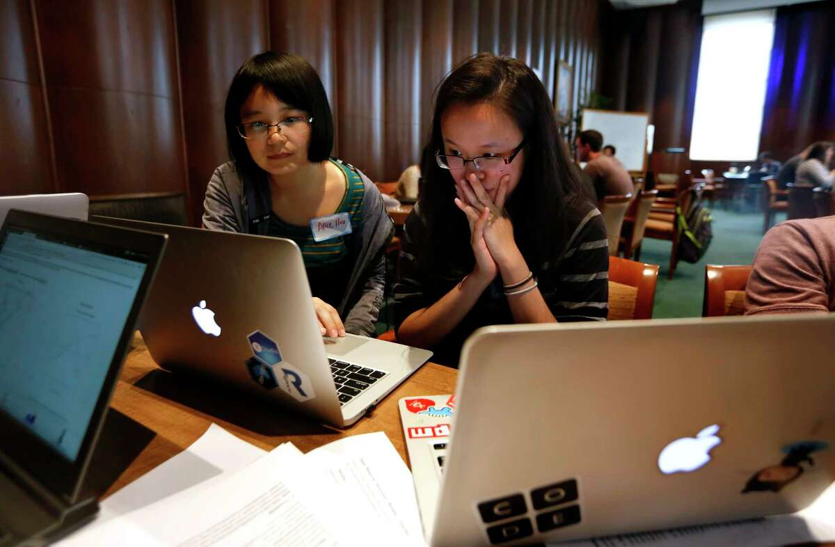Alice Hou and Amanda Shih work together on a laptop at Rice University's Fondren Library on Saturday.