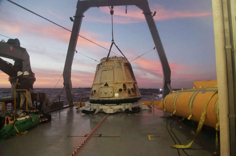 SpaceX's Dragon capsule sits aboard a ship in the Pacific Ocean after returning from the International Space Station in February 2015. SpaceX announced last Monday that it will send two paying customers to the moon next year on a private flight aboard its Dragon capsule. Photo: HONS / SpaceX
