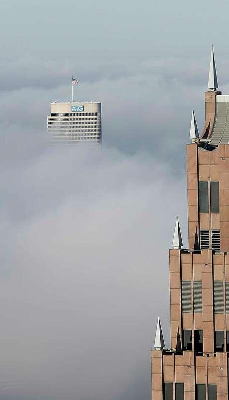The AIG building (Montrose); and Pennzoil Place (downtown). Photo: James Nielsen, Houston Chronicle / © 2015  Houston Chronicle