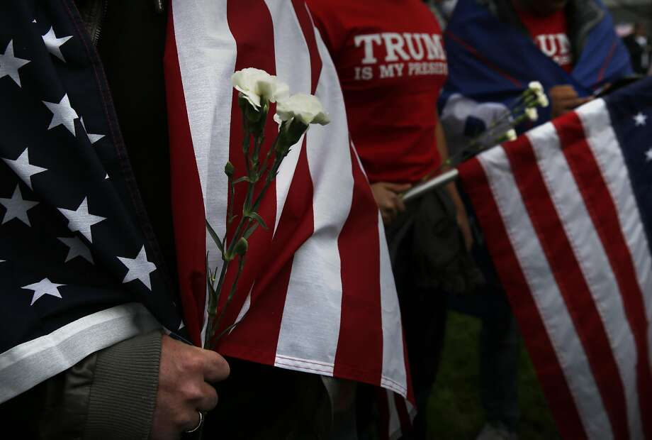 Trump supporter Lars Goller holds flowers an anti-Trump protester gave him during a pro-President Donald Trump rally and march at the Martin Luther King Jr. Civic Center park March 4, 2017 in Berkeley, Calif. Photo: Leah Millis, The Chronicle