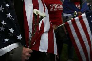 Trump supporter Lars Goller holds flowers an anti-Trump protester gave him during a pro-President Donald Trump rally and march at the Martin Luther King Jr. Civic Center park March 4, 2017 in Berkeley, Calif.