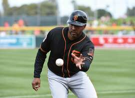 MESA, AZ - MARCH 03:  First base coach Jose Alguacil #17 of the San Francisco Giants makes a play on a bouncing foul ball during the first inning of a spring training game against the Oakland Athletics at HoHoKam Stadium on March 3, 2017 in Mesa, Arizona.  (Photo by Norm Hall/Getty Images)