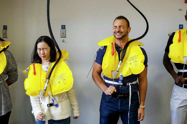 United Airlines flight attendant trainees Lauren Franco, left, Nicholas Villeneuve, second from right, and Mohamed Mbengue, right, pull the red tab to inflate their life vests as they test out the water evacuation equipment that they will be eventually showing passengers how to use Thursday, Oct. 13, 2016 in Houston. ( Michael Ciaglo / Houston Chronicle )
